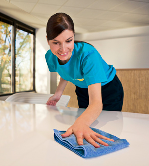 Janitorial cleaning professional wipes down meeting table in Lake Zurich